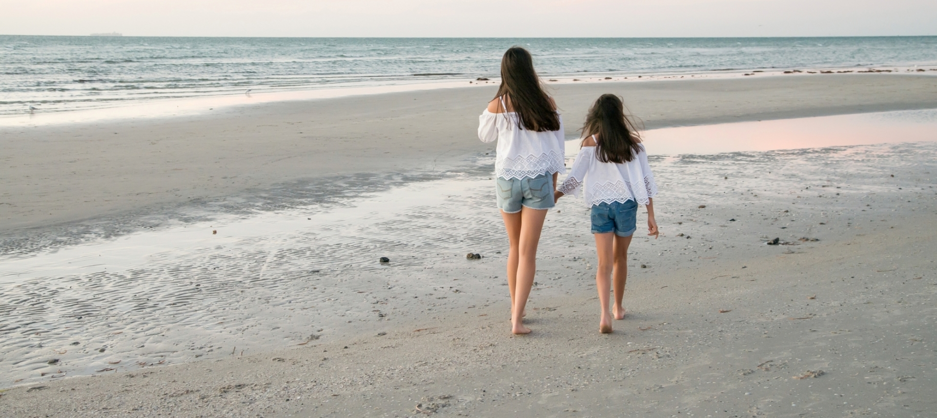 a photo of girls walking on a beach