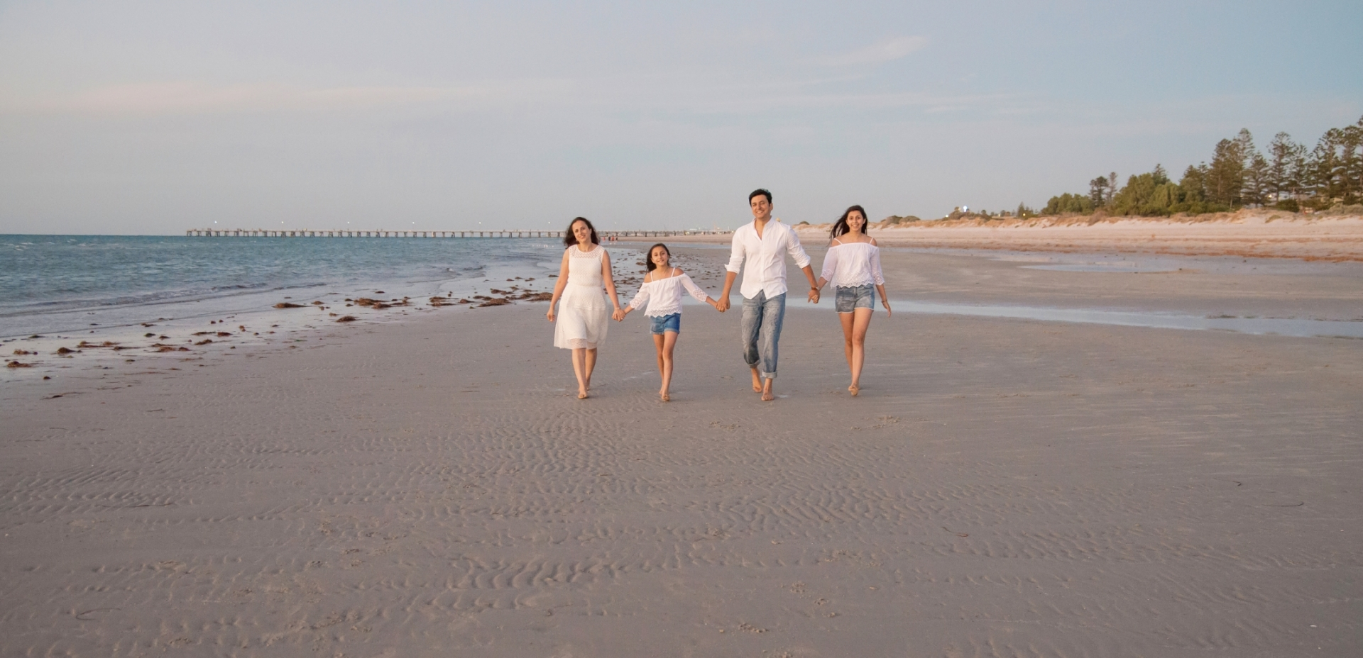 A photo of a family walking on a beach