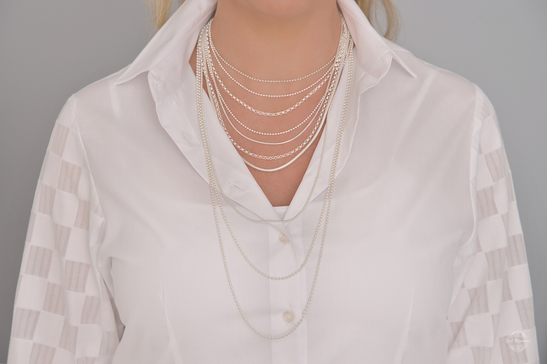 A photo of a woman wearing silver necklaces