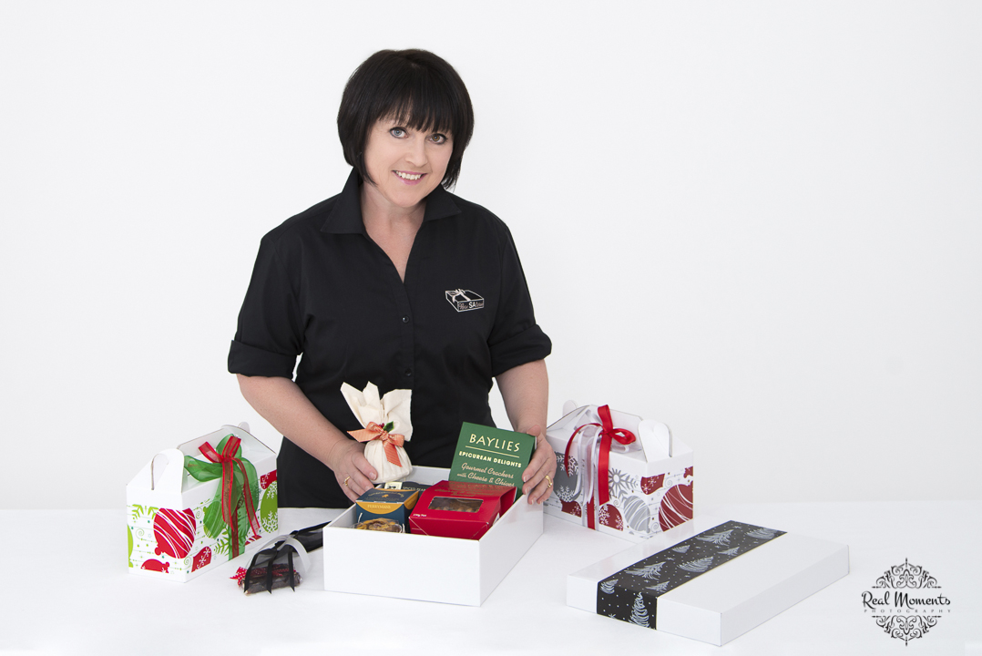 A corporate photo of boxsalicious' owner with products