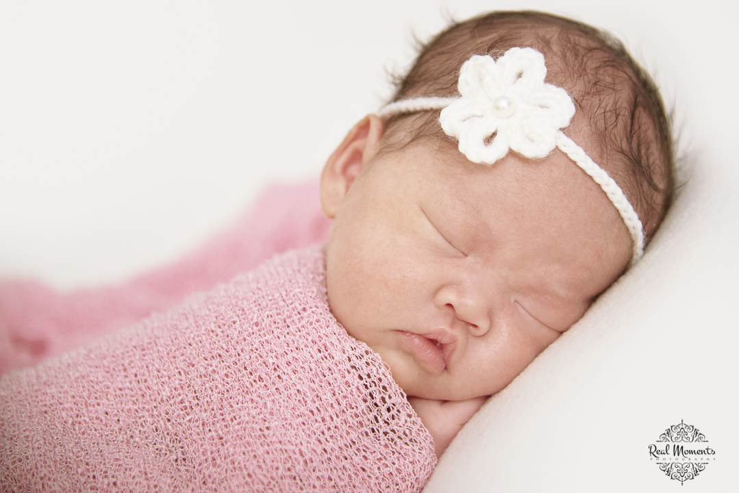 Another newborn photo of a baby girl wrapped in a pink cloth