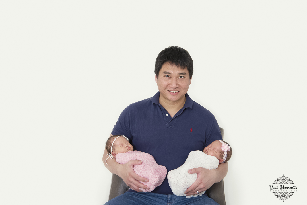 A newborn photo of twin girls with dad