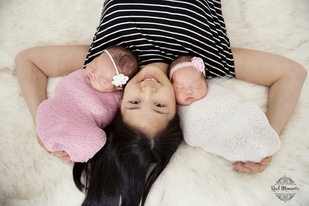 A newborn photo of twin girls with mom