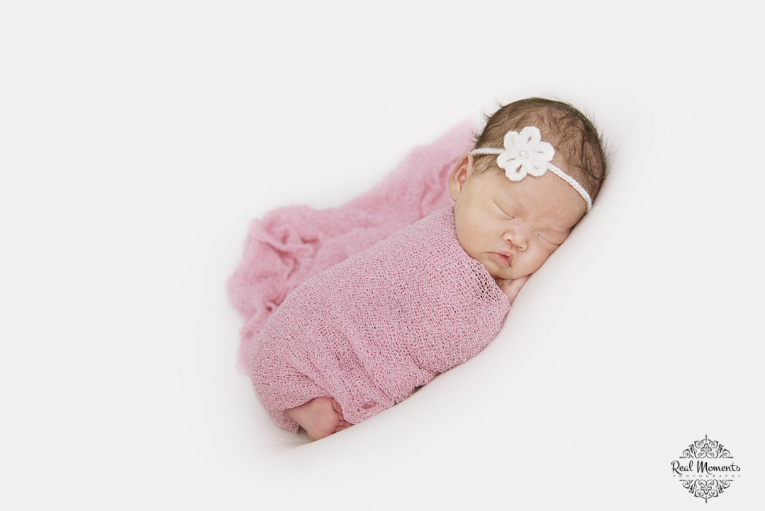 A newborn photo of a baby girl wrapped in a pink cloth