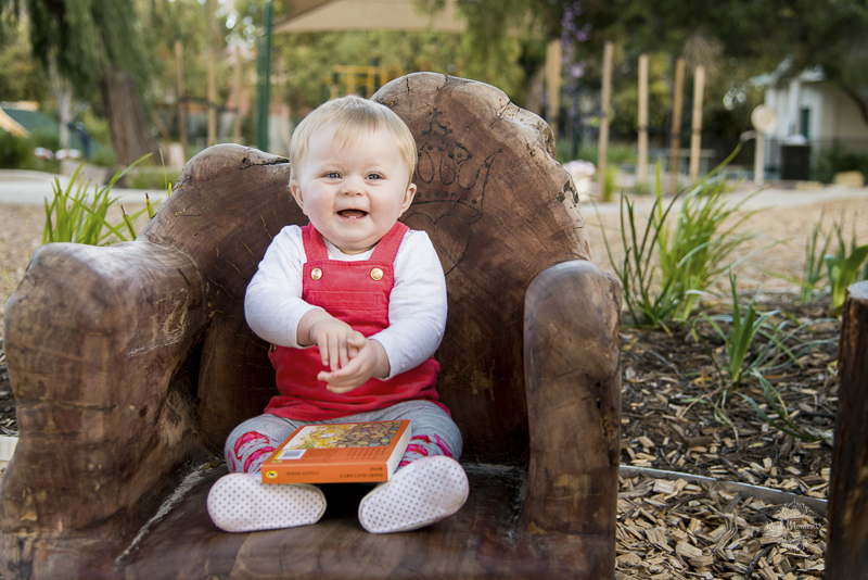A photo of a baby sitting on a chair