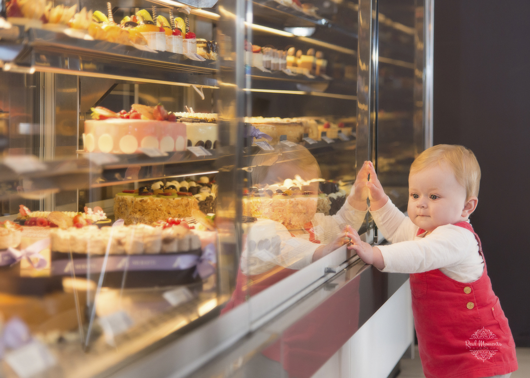 A portrait of baby looking at pastries