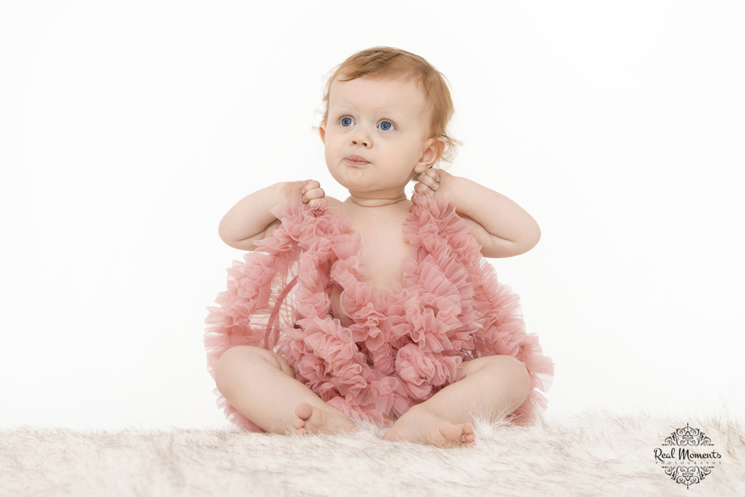 A photo of a baby with pink clothes